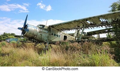 Rusty and broken planes stand in a field against a cloudy blue sky. Few destroyed abandoned planes