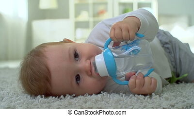 Abandoned Baby - Baby boy lying on the floor and drinking...