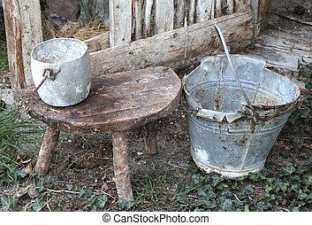 abandoned barn an old broken bucket and an aluminum pan