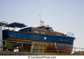 Abandoned boat - Old rusty fishing vessel sitting on pier