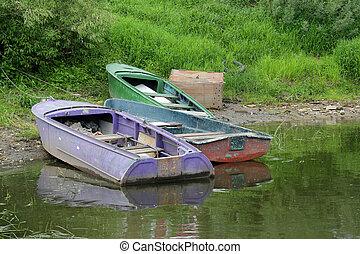 abandoned boats near the shore of T