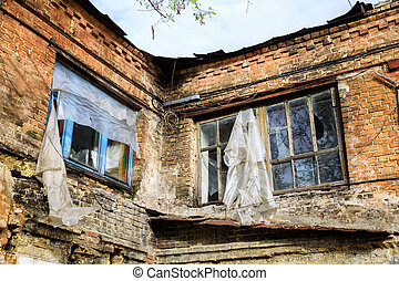 abandoned brick building - Broken windows with polyethylene...