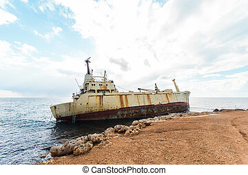Abandoned broken ship-wreck beached on rocky sea shore.