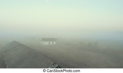 Abandoned buildings on an empty field in the fog. Aerial view