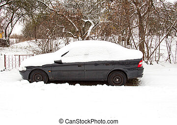 Abandoned car covered with snow