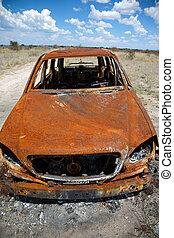 Abandoned Car in Field Under Blue Sky