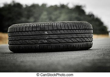 Abandoned car tyre on the road with green background