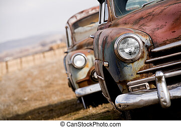 abandoned cars, two vintage cars angled closeup with focus...