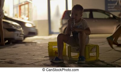 Abandoned child having snack sitting in the street