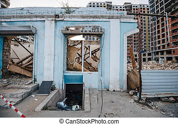 Abandoned destroyed old building in central Baku, Azierbaijan with tall construction apartment