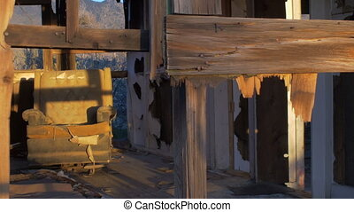 Abandoned dilapidated wood house with old ruined chair and...