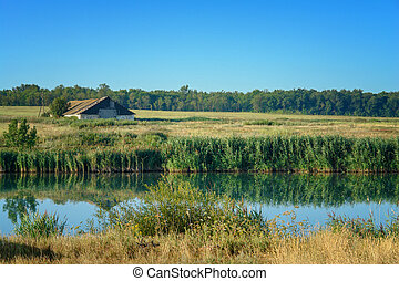 Abandoned farm or barn on the shore of small pond.