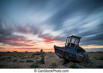 Abandoned fishing boat on beach landscape at sunset