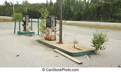 Abandoned gas station. - Abandoned gas pumps with overgrown...