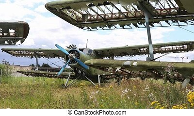 Abandoned green aircraft plane standing in the field against cloudy blue sky. Small propeller plane at the airplane cemetery