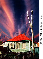Abandoned green wooden house with red roof opon dramatic sky