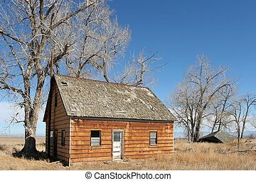 an abandoned, run down home in rural wyoming. broken-down shack in the background.