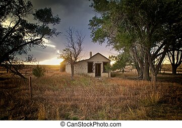 abandoned house at sunset with overcast sky