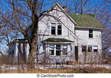 Abandoned rural home in disrepair with overgrown yard