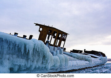 Abandoned iced barge on the shore of frozen lake