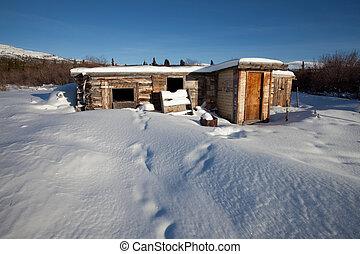 Abandoned log cabin in winter