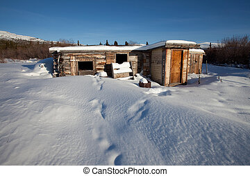 Abandoned log cabin in winter