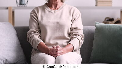Abandoned lonely elder lady sitting on sofa with hands ...
