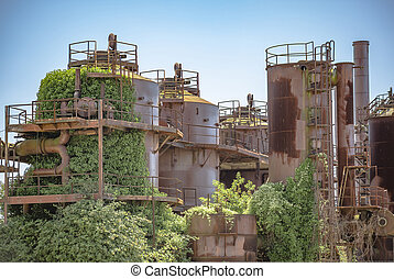 Abandoned machines and storage units in a gas industry at gas works park Seattle showing vine growth