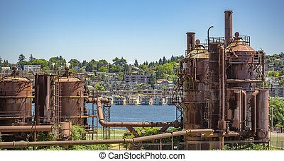 Abandoned machines and storage units in a gas industry at gas works park Seattle with homes behind