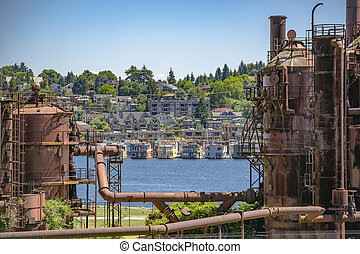 Abandoned machines and storage units in a gas industry at gas works park Seattle with water and homes