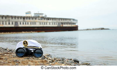 Abandoned obsolete steamboat - sailor cap and binoculars in...