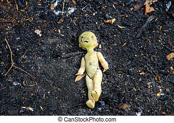 Abandoned old broken doll on grey ash background