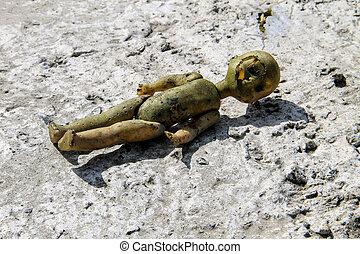 Abandoned old broken doll on grey concrete floor