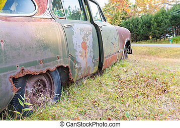 Abandoned old car decaying in the middle of a meadow
