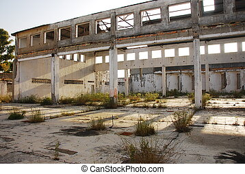 Very large, abandoned, old warehouse, machine shop or factory. Sun shines through broken windows. Large Pollution in Andalusia. Spain