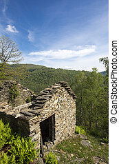 Abandoned old stones house with blue sky and forest