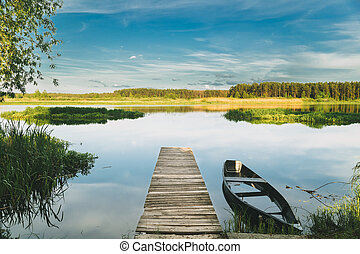 Old Wooden Fishing Boat Near Pier In Summer Lake Or River. Beautiful Summer Sunny Day Or Evening. Forsaken Boat. Russian Nature