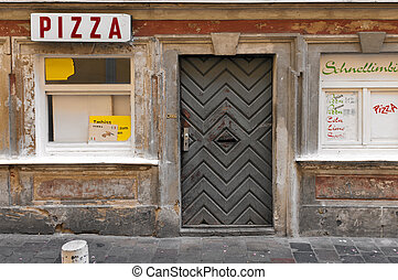 Abandoned pizzeria - Old worn pizzeria front boarded up,...