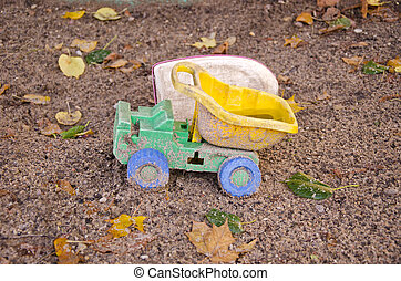 abandoned plastic truck toy in autumn sand box