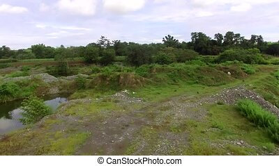 Abandoned quarry field at river side left by building...
