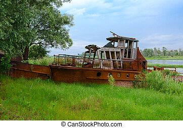 Abandoned rusty ship on river bank in exclusion zone of Chernobyl nuclear power plant, Belarus