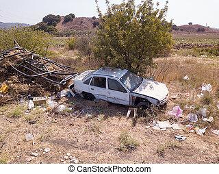 Abandoned rusty stolen cars in a junkyard. Scrap car.