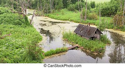 Abandoned sauna building on island on river
