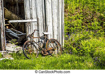 Abandoned shed in the Scottish Highlands with a broken rusted bike outside