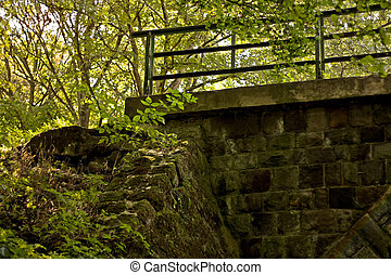 Abandoned stone bridge in deep forest with metal handrail...