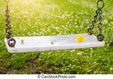 Abandoned swing with flowers in the spring season