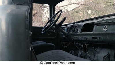 Abandoned truck interior with steering wheel, broken speedometer