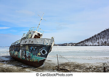 Abandoned vessel on the shore of frozen lake