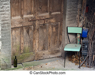 Abandoned village doorway with chair and wine bottle....