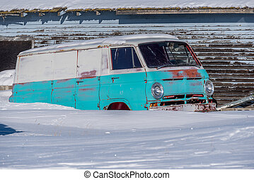 Abandoned vintage 1960?s blue and white van rusting in the snow of a Saskatchewan farmyard